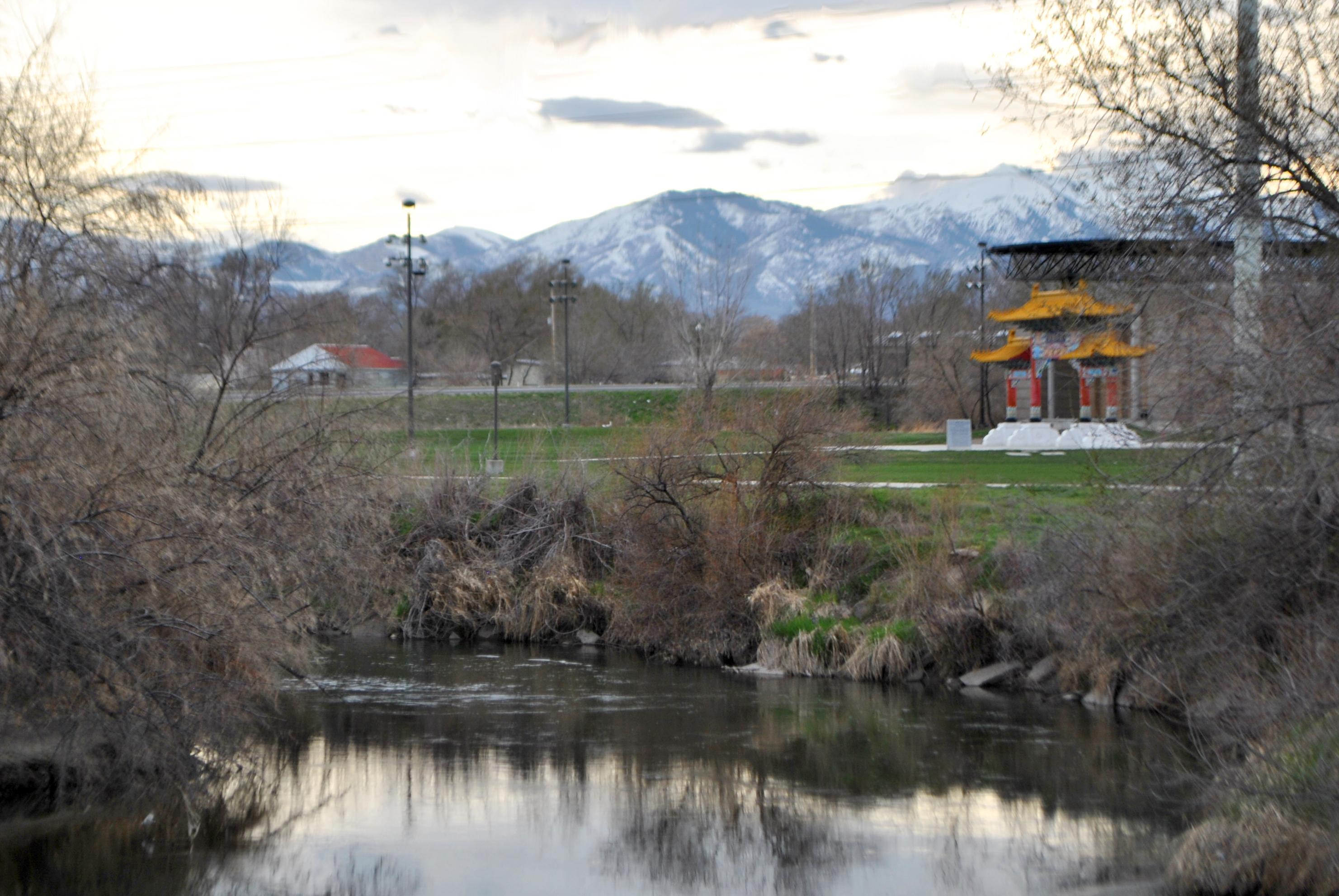 Jordan River in the foreground, Utah Cultural Celebration Center's grounds and mountains in the background